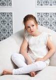 Mädchenmodeporträt Kindervorbildliches Sitzen im Stuhl Stockfotografie
