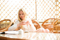Mädchenmorgenkaffee in der hellen warmen Atmosphäre Lizenzfreie Stockfotografie