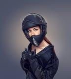 Mädchenmotorradfahrer in einer schwarzen Jacke und in einem Sturzhelm Lizenzfreie Stockfotografie