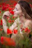 Mädchennahaufnahmeportrait in den Mohnblumen Stockfoto