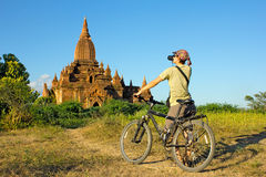 Mädchenphotograph auf einem Fahrrad macht ein Foto des Tempels herein stockbilder