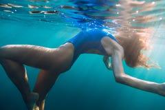 Mädchenporträt, das unter Wasser mit blauem Bikini aufwirft Frau im Ozean lizenzfreie stockfotos