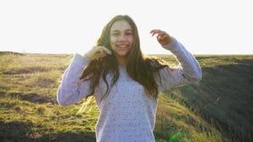 Mädchenporträt-Lächelngefühle in den Sonnenuntergangsonnenlichtstrahlen Naturhils und -feld stock video footage