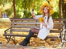 Mädchenporträt mit Blättern auf dem Kopf, der selfie im Herbststadtpark nimmt Lizenzfreie Stockfotos