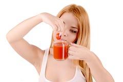 Mädchenpressungen des Tomatensafts Stockbild