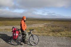 Mädchenradfahrer auf dem Hintergrund der Tundra Stockbild