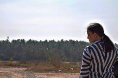 Mädchenradfahrer, der ihren Sturzhelm hält und für ein Bild in der breiten Landschaft aufwirft lizenzfreie stockbilder
