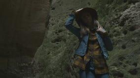 Mädchenreisender in einer Höhle oder in einer Schlucht Sie trägt einen Hut und eine Jacke und hat einen Rucksack Erforscht eine a stock footage
