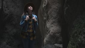 Mädchenreisender in einer Höhle oder in einer Schlucht Sie trägt einen Hut und eine Jacke und hat einen Rucksack Erforscht eine a stock video footage