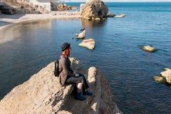 Mädchenreisender sitzt auf einem Felsen Lizenzfreies Stockbild