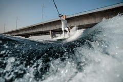 Mädchenreiten auf dem wakeboard, das ein Seil hält lizenzfreie stockfotos