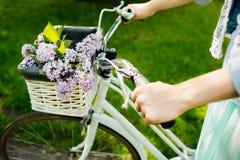 Mädchenreiten auf einem Fahrrad mit Blumen Lizenzfreies Stockfoto