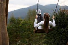 Mädchenreiten auf einem Schwingen mit Karpaten-Berg auf dem Hintergrund Glückliche Frau genießt und entspannt sich auf ihren Feri Lizenzfreies Stockbild