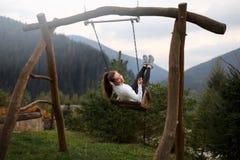 Mädchenreiten auf einem Schwingen mit Karpaten-Berg auf dem Hintergrund Glückliche Frau genießt und entspannt sich auf ihren Feri Lizenzfreie Stockfotos