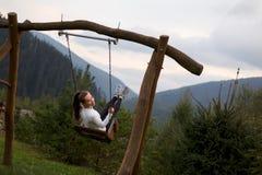 Mädchenreiten auf einem Schwingen mit Karpaten-Berg auf dem Hintergrund Glückliche Frau genießt und entspannt sich auf ihren Feri Lizenzfreies Stockfoto