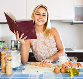 Mädchenrollenteig am Küchentisch stockfoto