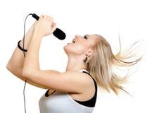 Mädchensänger, der zum Mikrofon auf Weiß singt Stockfotografie