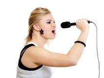 Mädchensänger, der zum Mikrofon lokalisiert auf Weiß singt Lizenzfreie Stockfotografie