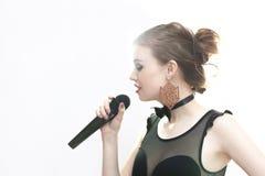 Mädchensänger mit einem Mikrofon auf einem weißen Hintergrund Stockfotografie