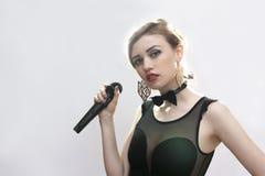 Mädchensänger mit einem Mikrofon auf einem weißen Hintergrund Stockbild