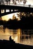 Mädchenschattenbild auf dem Sonnenuntergang nahe Wasser lizenzfreies stockbild