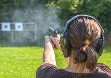 Mädchenschießen mit einem Gewehr lizenzfreie stockfotografie