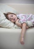 Mädchenschlaf auf Sofa Lizenzfreie Stockfotos