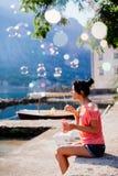 Mädchenschlagblasen auf Strand Stockbilder