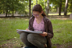 Mädchenschreiben auf ihrem Notizbuch Stockfotos