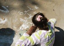 Mädchenschreibensgraffiti mit weißer Kreide aus den Grund in einem Camping-Ausflug in Ägypten Lizenzfreie Stockfotos