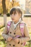 Mädchenschulmädchen mit einem warmen Herbsttag des Rucksacks Lizenzfreie Stockfotografie