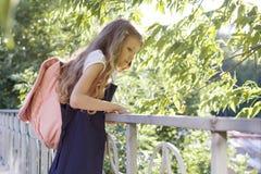M?dchenschulm?dchenblondine mit Rucksack in der Schuluniform nahe Zaun im Schulhof lizenzfreie stockfotografie