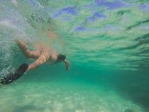 Mädchenschwimmen im Ozean stockfotografie