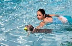 Mädchenschwimmen mit Hund Lizenzfreie Stockfotos