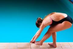 Mädchenschwimmer, der zum Springen und zum Tauchen sich vorbereitet Stockfotografie
