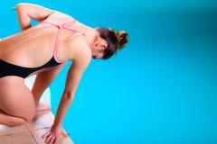 Mädchenschwimmer, der zum Springen und zum Tauchen sich vorbereitet Lizenzfreie Stockfotos