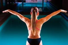 Mädchenschwimmer, der zum Springen und zum Tauchen sich vorbereitet Lizenzfreies Stockfoto