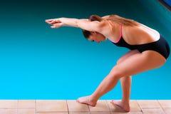Mädchenschwimmer, der zum Springen und zum Tauchen sich vorbereitet Stockfotos