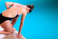 Mädchenschwimmer, der zum Springen und zum Tauchen sich vorbereitet Stockfoto