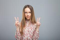 Mädchenshowgeste des Friedens Lizenzfreies Stockfoto