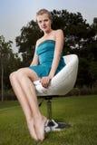 Mädchensitzen im Freien auf einem Schwenkerstuhl lizenzfreies stockfoto