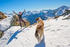 Mädchenski, der in die Berge mit Hund bereist lizenzfreies stockfoto