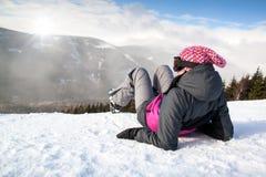 Mädchenskifahrer, der auf Schnee ohne Ski, Berg liegt Lizenzfreies Stockbild