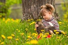 Mädchenspaß, der mit einer Katze im Garten spielt Stockfotografie