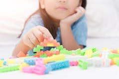 Mädchenspiel-Blockziegelsteine auf Bett, Bildung Lizenzfreie Stockbilder