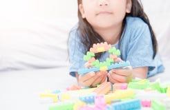 Mädchenspiel-Blockziegelsteine auf Bett, Bildung Stockfotos