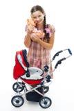 Mädchenspiel mit Buggy und Puppe Stockfotografie