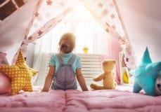 Mädchenspiel zu Hause Stockbilder