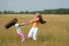 Mädchenspiele auf einer Wiese Stockfotografie