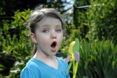 Mädchenspiele mit einer Windmühle Lizenzfreie Stockfotografie